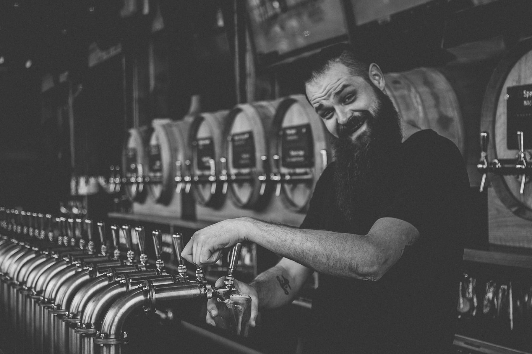 A bartender pouring beer from taps