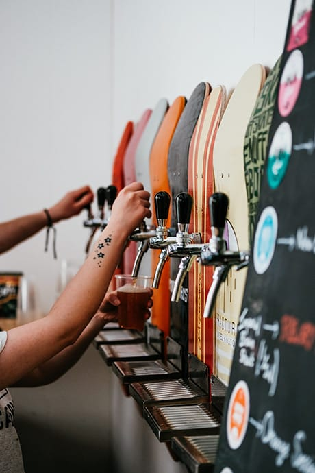 People drinking beer from skateboards